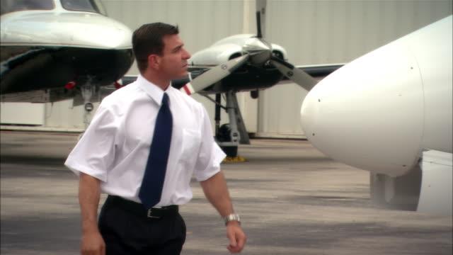 medium shot pilot inspecting private jet outside hangar at opa locka airport/ miami, florida, usa - skjorta och slips bildbanksvideor och videomaterial från bakom kulisserna