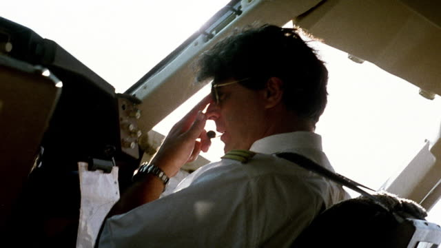 medium shot pilot sitting in cockpit with sun flare - piloting stock videos and b-roll footage