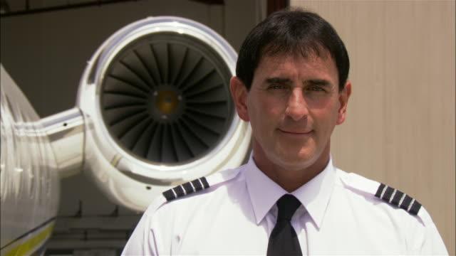 stockvideo's en b-roll-footage met medium shot pilot smiling and entering private airplane / long beach, california, usa - overhemd en stropdas