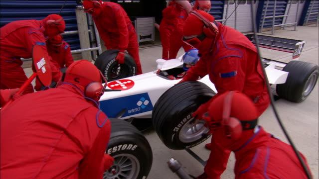 vídeos y material grabado en eventos de stock de medium shot pit crew changing tires on formula one car during pit stop - formula 1