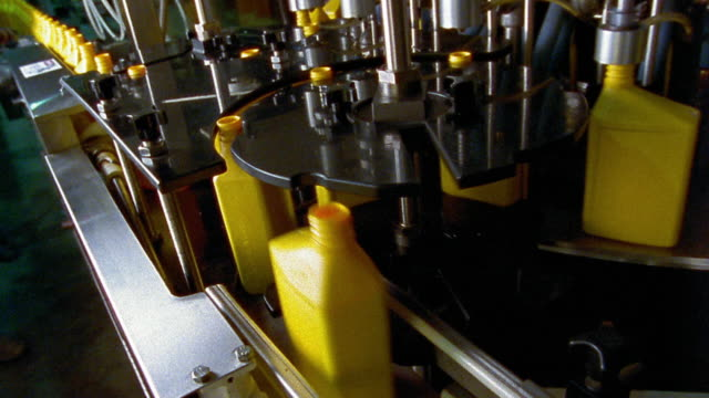 medium shot plastic yellow motor oil bottles moving on conveyor belts - lubrication stock videos & royalty-free footage