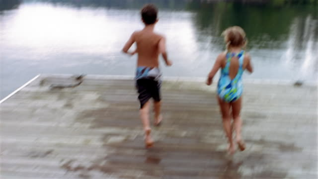 vídeos de stock e filmes b-roll de medium shot point of view boy and girl in swimsuits running to end of dock + jumping into lake / high angle ms swimming - pontão