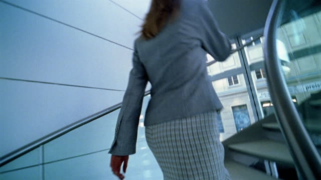 medium shot point of view businesswoman walking spiral staircase while talking on mobile phone / berlin - spiral staircase stock videos & royalty-free footage
