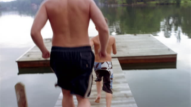 Medium shot point of view father and son running to end of dock + jumping into lake / high angle MS treading in water