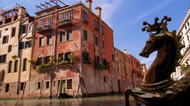 Medium shot point of view gondola with gold sea horse ornament on canal passing buildings / Venice