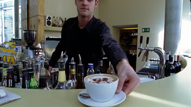 vídeos de stock, filmes e b-roll de medium shot point of view man serving coffee at cafe / berlin - só um homem jovem
