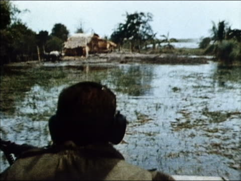 vidéos et rushes de 1964 medium shot point of view over the shoulder of soldier piloting boat over marshland / vietnam - 1964