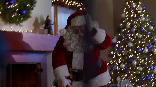 medium shot point of view santa claus hushing at cam and placing christmas gifts under christmas tree / mexico city - sacca video stock e b–roll