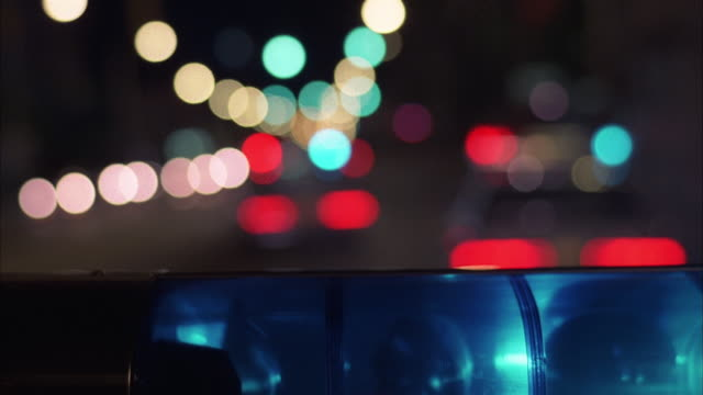 medium shot police car point of view rack focus driving behind police cars with flashing lights on street at night / miami - police car stock videos & royalty-free footage