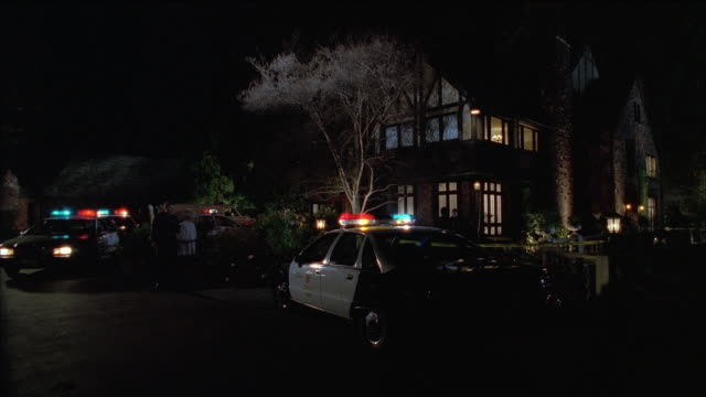 vidéos et rushes de medium shot police cars with lights flashing and cops gathered outside suburban home / british columbia, canada - meurtre