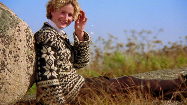 Medium shot portrait blonde teen girl in sweater sitting leaning against boulder and smiling / Nova Scotia