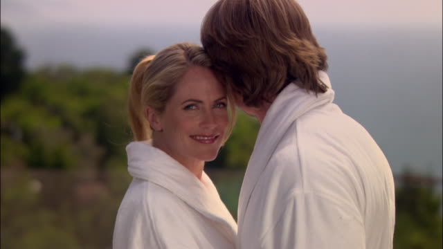 medium shot portrait couple kissing in robes at spa/ monterey county, california - ragged point stock videos and b-roll footage