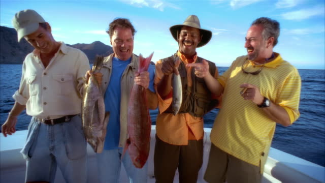 medium shot portrait four men on fishing boat smiling and holding up their fish/ long beach, california - cinquantenne video stock e b–roll