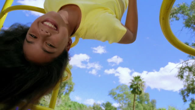 medium shot portrait girl swinging upside down on monkey bars and smiling / tucson, arizona - ジャングルジム点の映像素材/bロール