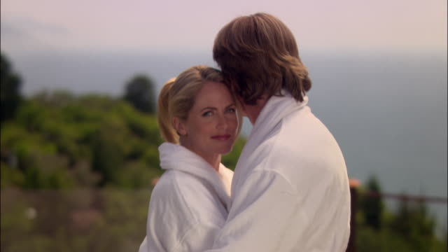 medium shot portrait man and woman hugging in robes at spa/ monterey county, california - ragged point stock videos and b-roll footage