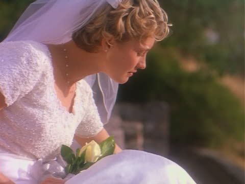 medium shot portrait of a young blonde bride in her wedding dress and veil as she turns and smiles into the camera