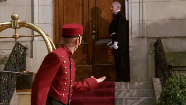 Medium shot portrait of bellman smiling and welcoming guest to hotel / gesturing to doorman opening door