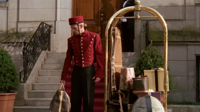 Medium shot portrait of bellman standing near luggage cart / putting bag down and straightening uniform