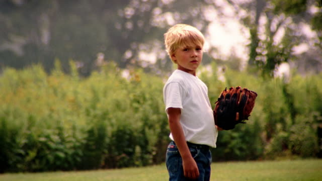 vídeos de stock, filmes e b-roll de medium shot portrait of boy wearing baseball glove / holding baseball - da cintura para cima