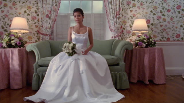 stockvideo's en b-roll-footage met medium shot portrait of bride wearing gown sitting on sofa and holding bouquet / looking at cam + smiling - 2005