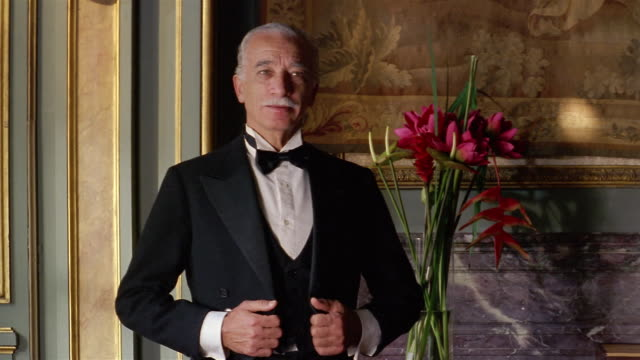 medium shot portrait of butler / straightening jacket and looking at cam / vase of flowers in background - domestic staff stock videos & royalty-free footage