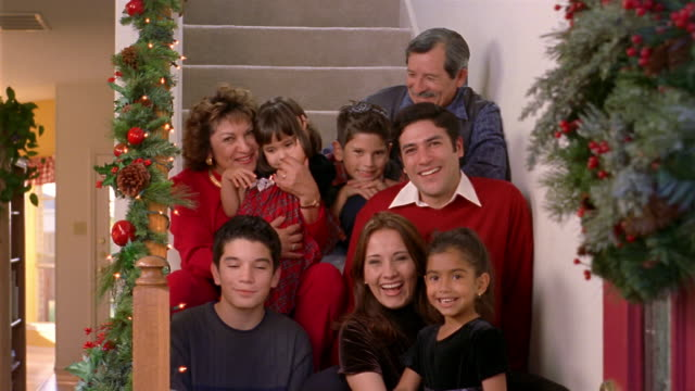 vídeos de stock e filmes b-roll de medium shot portrait of family sitting on staircase during christmas holiday season - família com quatro filhos