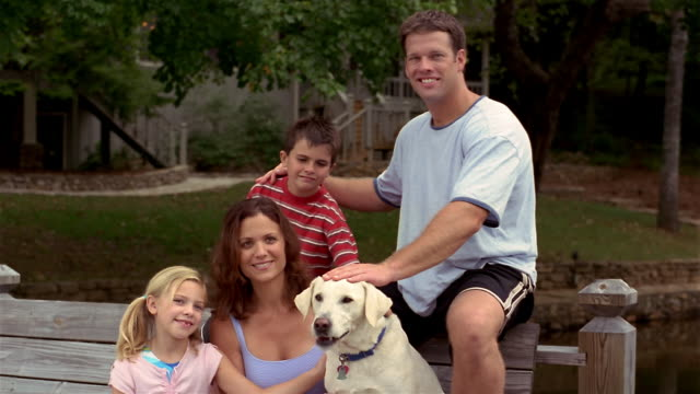 medium shot portrait of family with pet labrador retriever / playground in background - family with two children stock videos & royalty-free footage