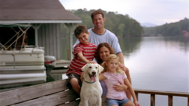 medium shot portrait of family with pet labrador retriever sitting on dock - clarkesville stock videos & royalty-free footage