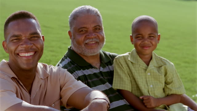 stockvideo's en b-roll-footage met medium shot portrait of father, grandfather and son sitting on lawn + smiling at cam - wit haar