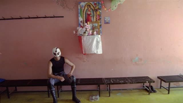 stockvideo's en b-roll-footage met medium shot portrait of luchador 'cometa negro' on bench under altar of catholic saint / queretaro, mexico - altaar