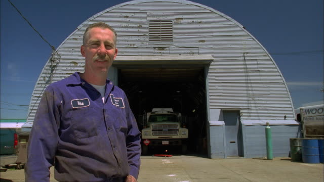 Medium shot portrait of mechanic standing outside garage hangar w/truck in background