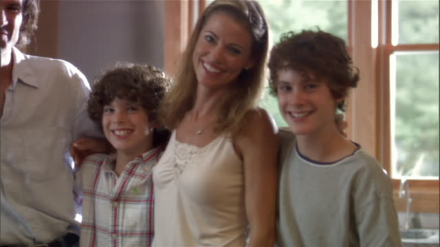 medium shot portrait of parents and two sons in kitchen with their arems around each other smiling - arm around stock videos & royalty-free footage