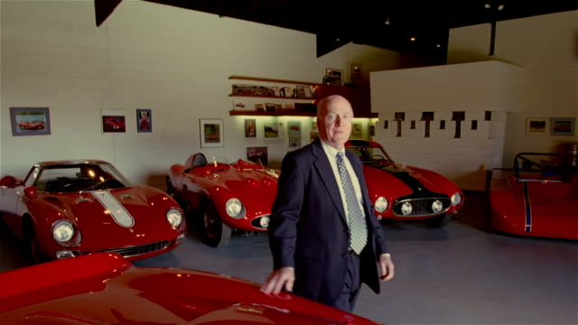 medium shot portrait of senior man in garage surrounded by vintage cars / arms folded and looking at camera - showroom stock videos and b-roll footage