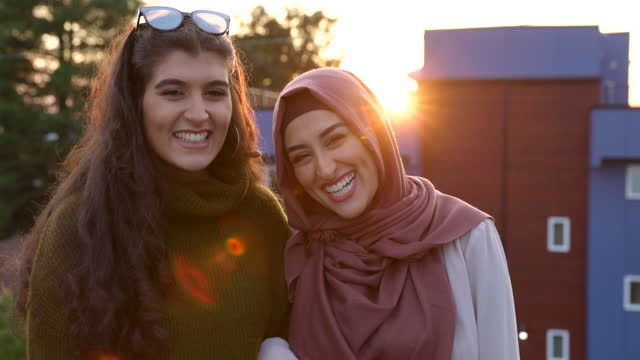 medium shot portrait of sisters relaxing on rooftop deck at sunset - hijab stock videos & royalty-free footage
