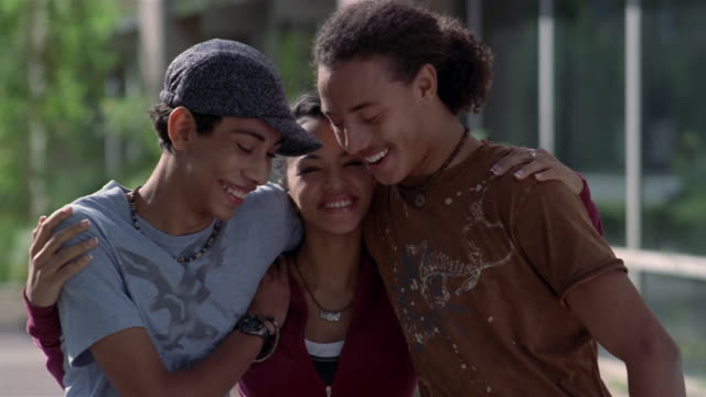 Medium shot portrait of teenage boys and girl smiling at camera and hugging each other