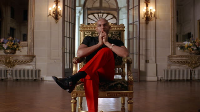 vídeos y material grabado en eventos de stock de medium shot portrait of wealthy man in trendy clothing sitting in gilded chair in foyer of mansion - camiseta