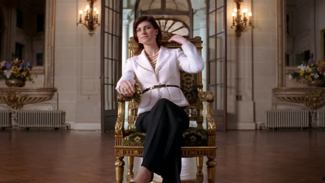 vídeos de stock e filmes b-roll de medium shot portrait of wealthy woman sitting in gilded chair in foyer of mansion - mansão imponente