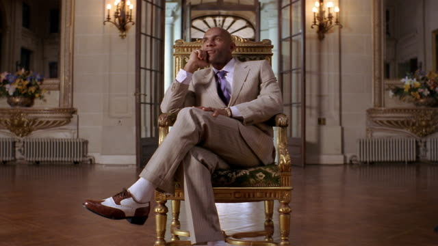 stockvideo's en b-roll-footage met medium shot portrait of well-dressed man in contemplative pose on gilded chair in mansion / looking at cam - tuindeur