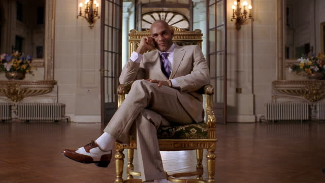 Medium shot portrait of well-dressed man sitting in gilded chair in foyer of mansion