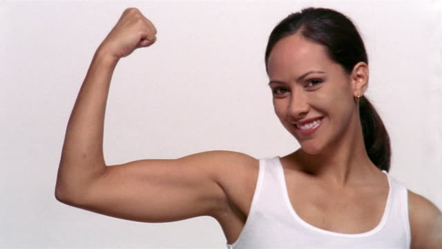 Medium shot portrait of woman smiling and making a muscle