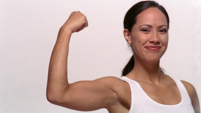 medium shot portrait of woman smiling and making a muscle - bicep stock videos and b-roll footage