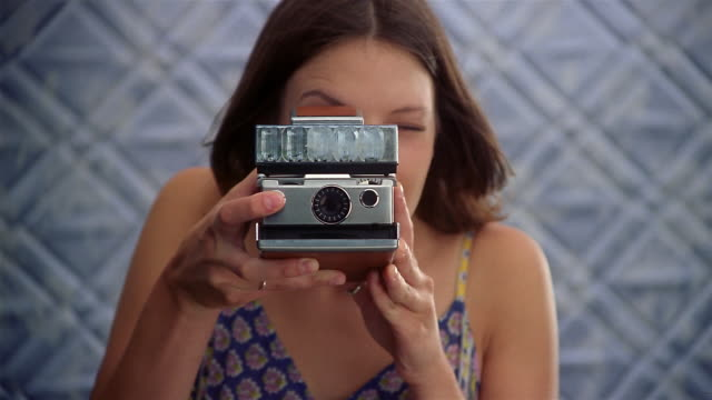 Medium shot portrait of woman smiling at CAM / taking picture with Polaroid camera / tossing photo at CAM / low angle