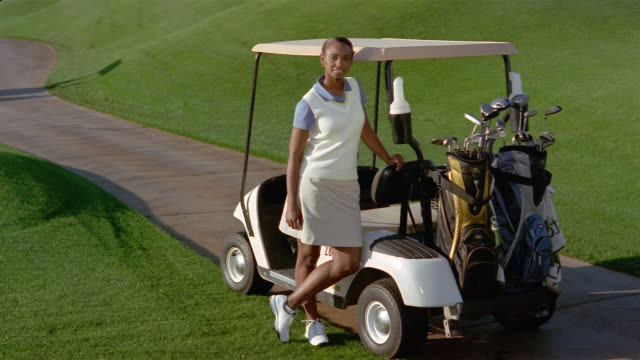 vídeos de stock, filmes e b-roll de medium shot portrait of woman standing next to golf cart and smiling at camera - bolsa de golfe