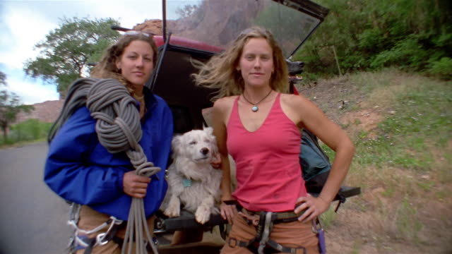 medium shot portrait of women rock climbers leaning on back of car with trunk open / dogs in background - vest stock videos & royalty-free footage