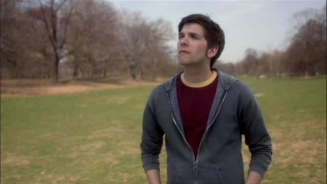 vídeos y material grabado en eventos de stock de medium shot portrait of young man looking up at the sky in park - mirar hacia arriba