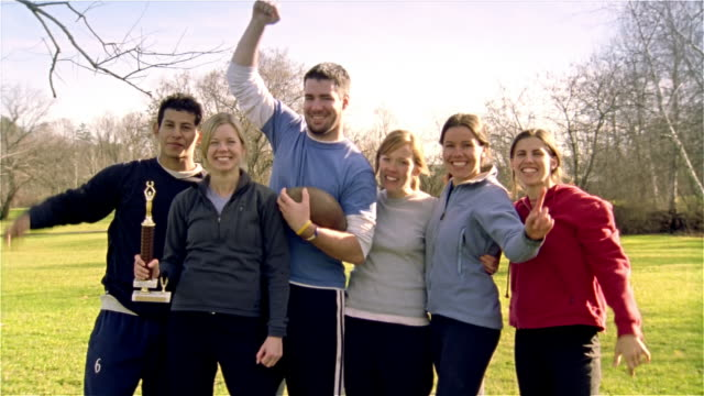 medium shot portrait touch football team with arms in air and woman holding trophy/ maine - touch football video stock e b–roll
