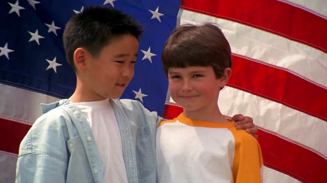 medium shot portrait two young boys smile and embrace in front of american flag - arm around stock videos & royalty-free footage