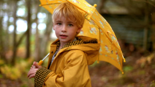 Medium shot portrait young blonde girl in raincoat holding umbrella turning to camera outdoors / Nova Scotia