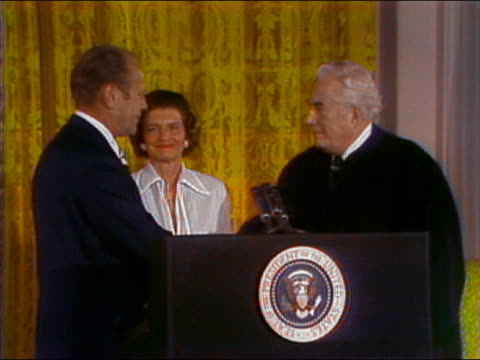 1974 medium shot President Ford shaking chief Justice Burger's hand and kissing Betty Ford at inauguration