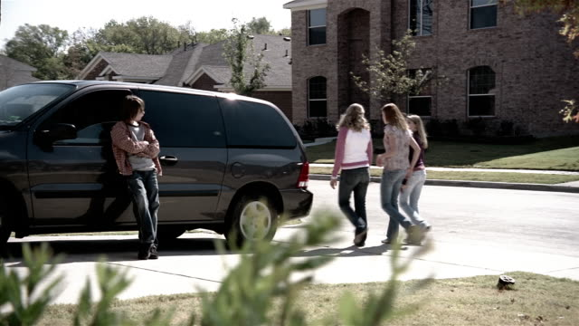 Medium shot pre-teen boy leaning against minivan / teenage girls walking by